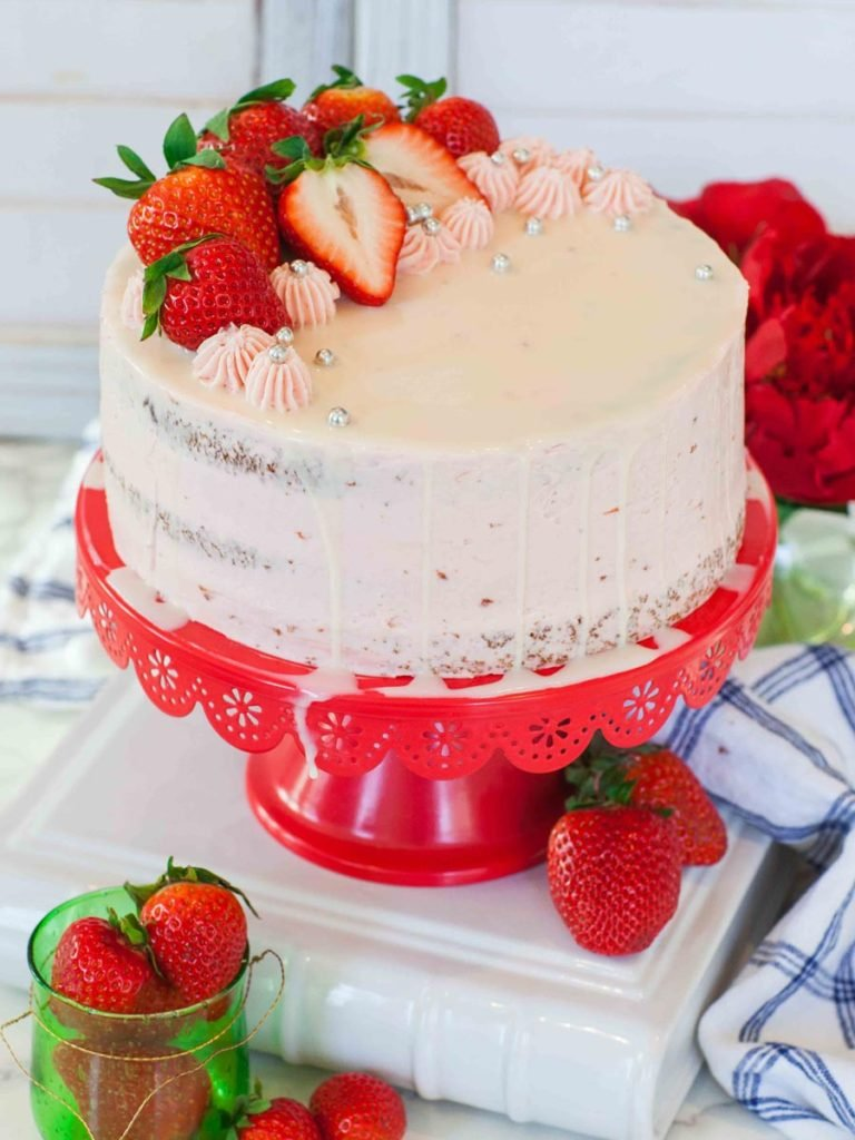 Strawberry Basil Cake topped with strawberries on red cake stand
