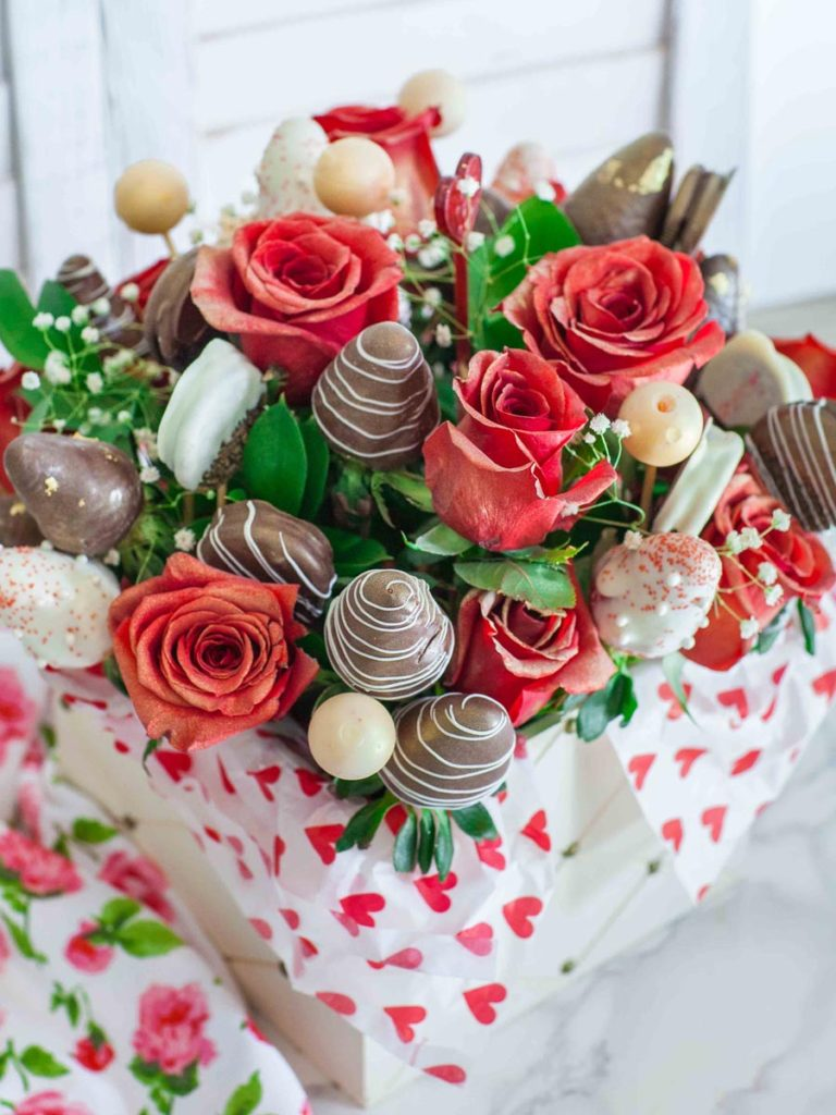 edible arrangement with roses, strawberries, cookies and truffles
