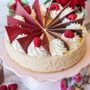 no-bake caramel cheesecake with raspberry filling, chocolate garnishes and whipped cream