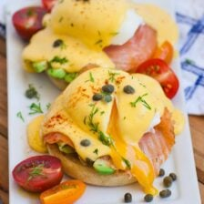 A plate of smoked salmon eggs benedict, with tomatoes