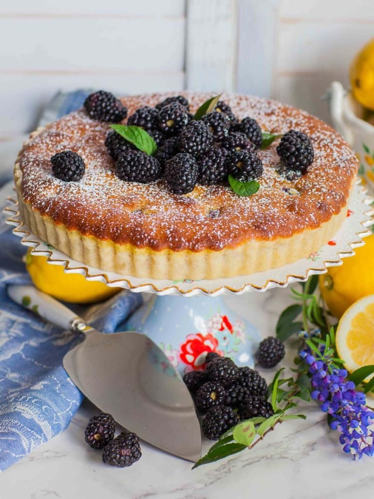 lemon almond tart with blackberries on floral cakestand