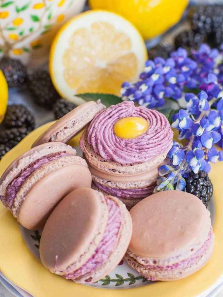 lavender french macarons with lemon center on tray with lemons