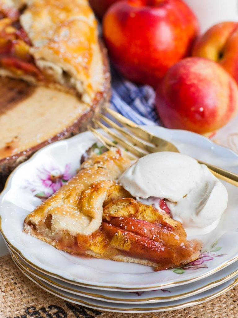 slice of peach galette with ice cream and fresh peaches