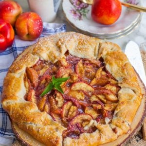 peach galette with fresh peaches on rustic board