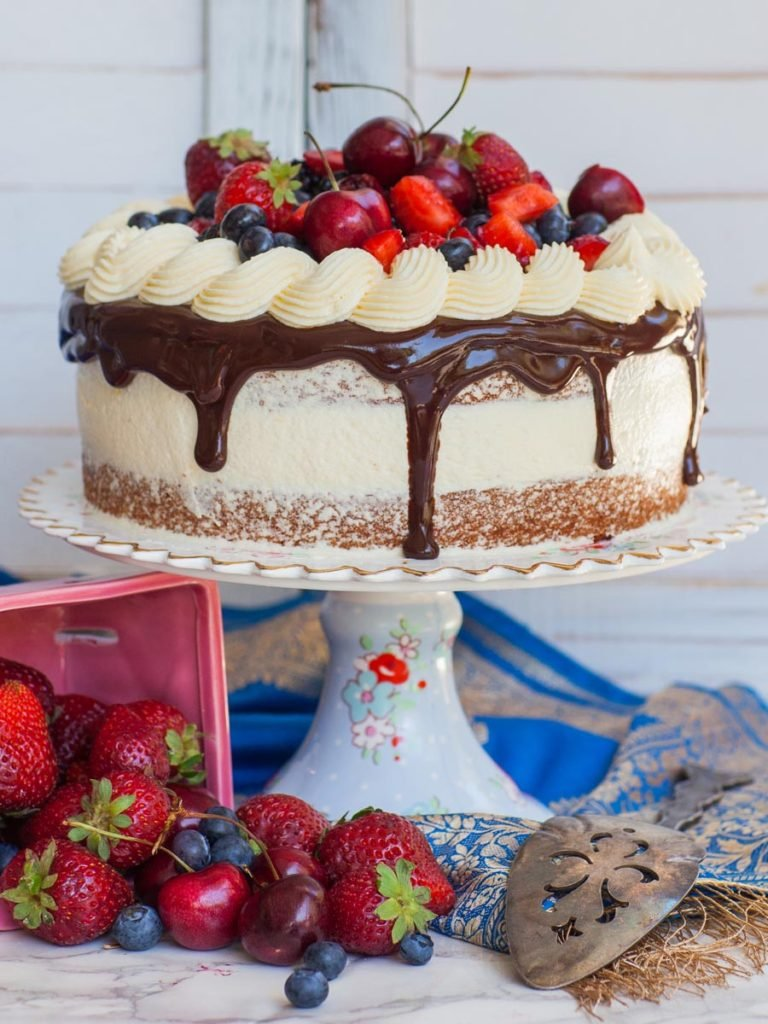 berry almond cake on floral cake stand with strawberries