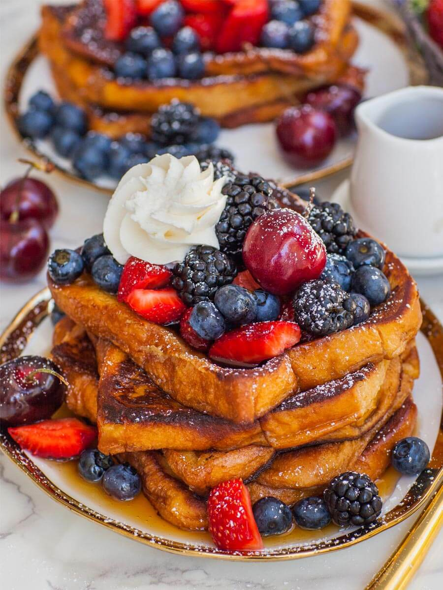 pan-fried french toast stacked on tray with berries, maple syrup and whipped cream
