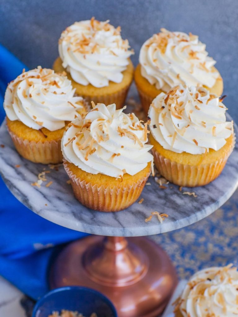 fluffy coconut cupcakes with coconut buttercream and toasted coconut on marble cake stand