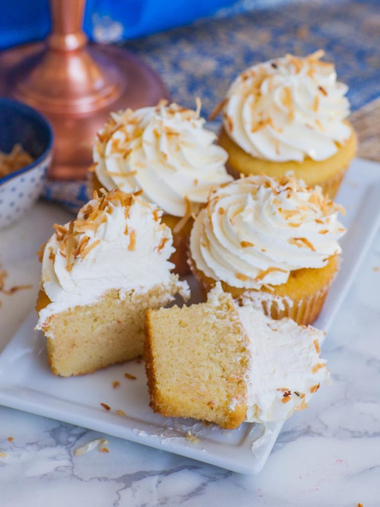 coconut cupcake cut in half on tray with italian meringue buttercream