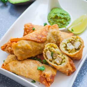 egg rolls split in half on white tray with dipping sauce