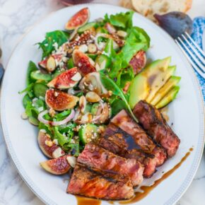 green salad with figs and sliced steak with wine and baguette
