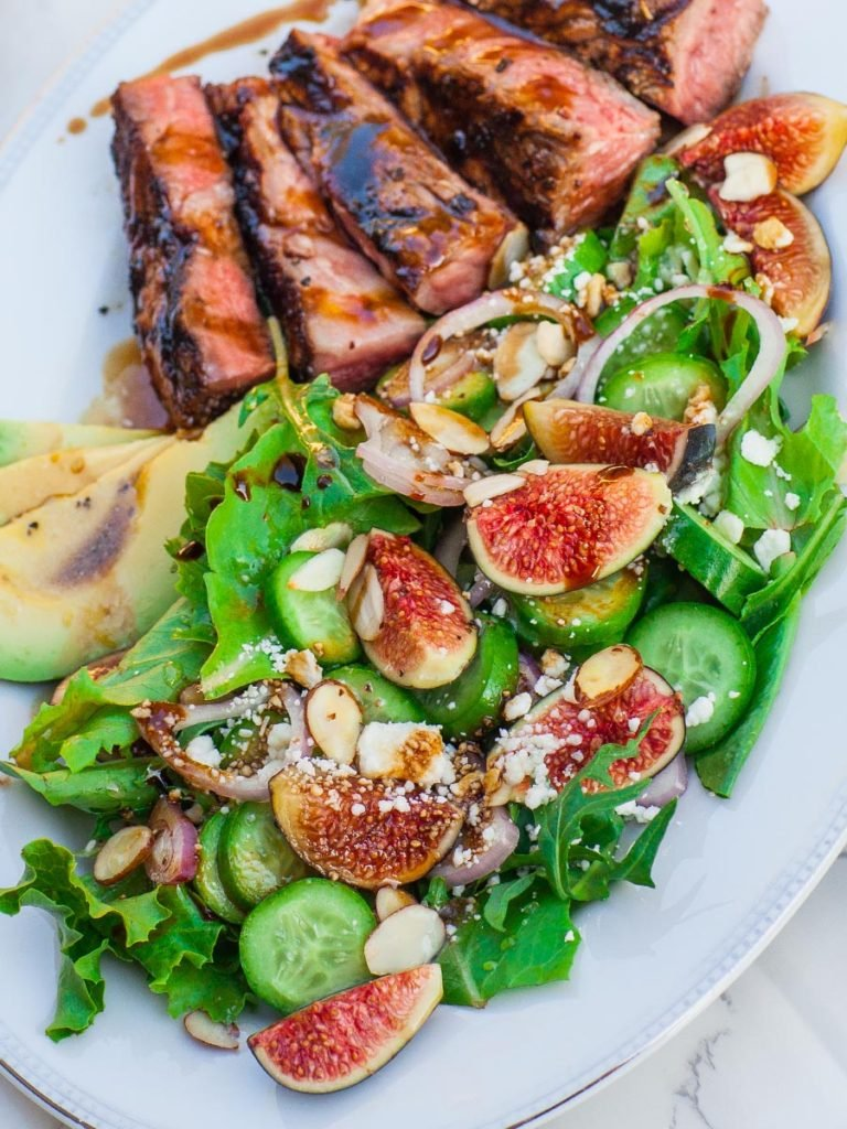 fig salad with steak topped with mission figs, cucumbers, shallots, avocado and cheese