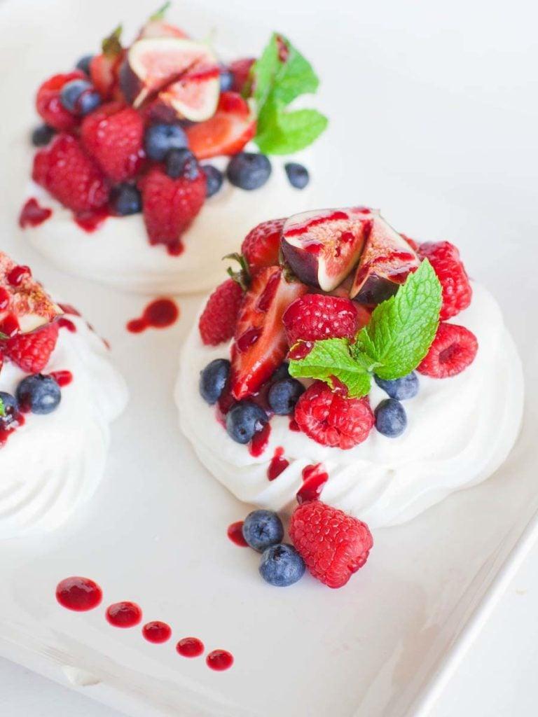 mini pavlova topped with cream, berries and raspberry sauce