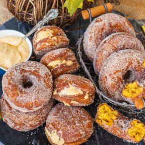 cinnamon sugar coated pumpkin donuts on black marble tray