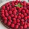 chocolate tart with chocolate filling topped with fresh raspberries