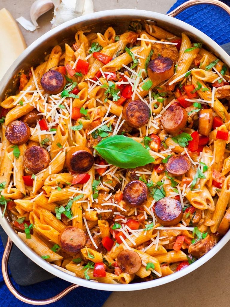 pepper pasta with sausage in skillet, topped with parmesan cheese and basil