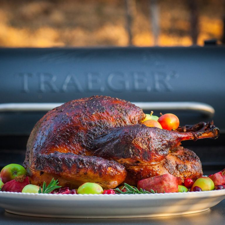 smoked turkey on serving platter with Traeger smoker