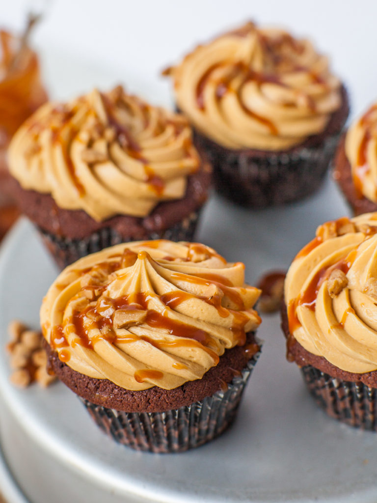 chocolate toffee cupcakes with caramel frosting and caramel drizzle