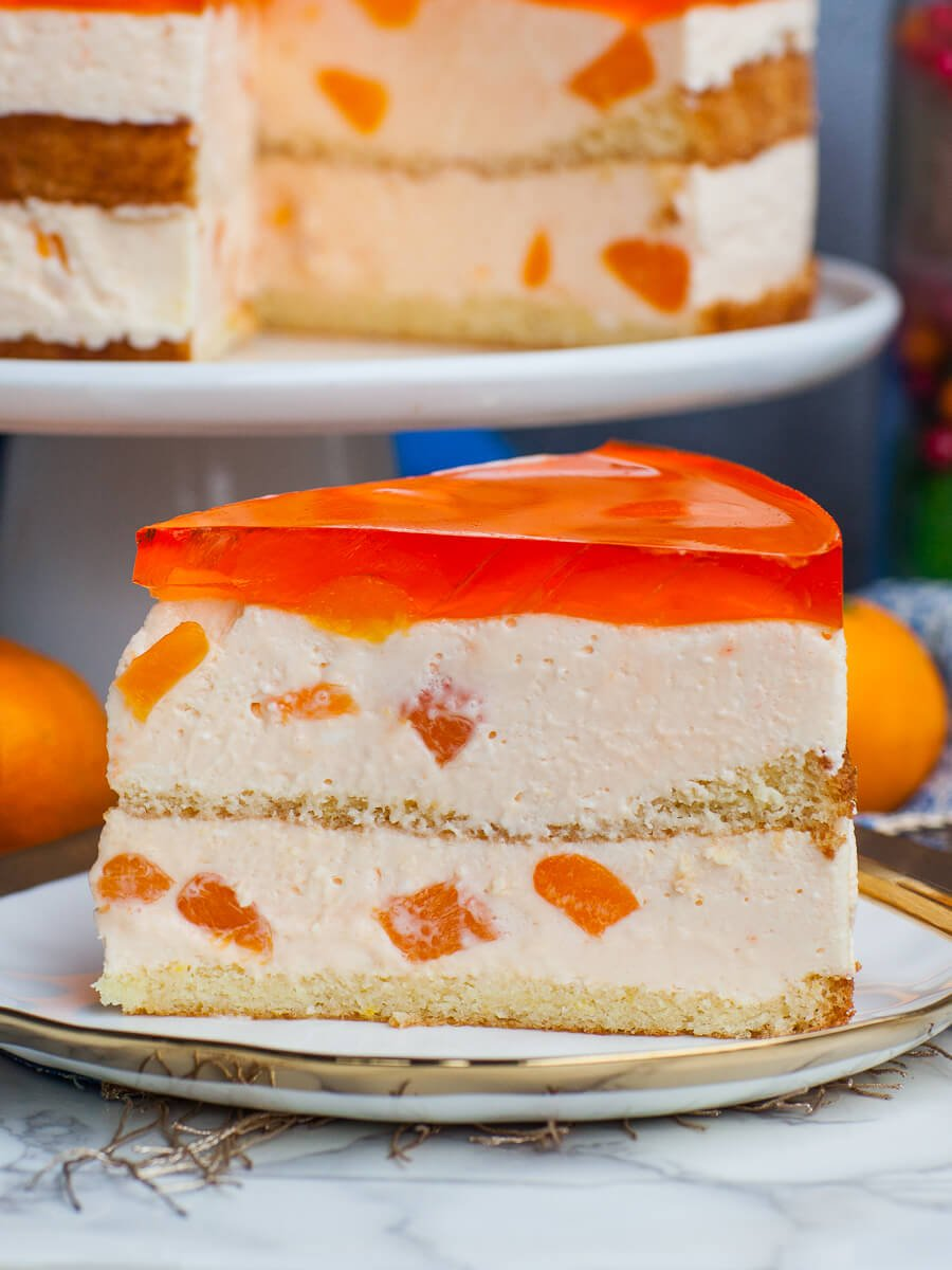 closeup citrus mousse cake slice with mandarins
