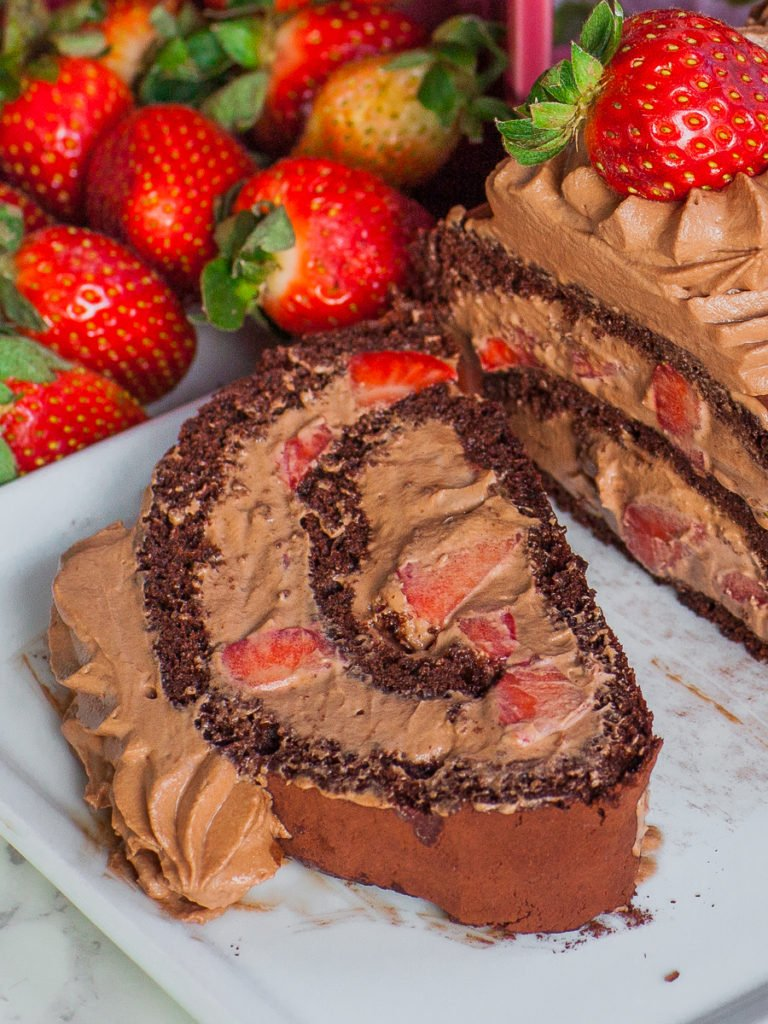 slice of chocolate cake roll with nutella whipped cream and strawberries; chocolate roulade
