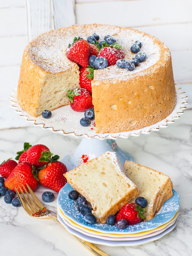white sponge cake on a floral cake stand with berries; angel food cake