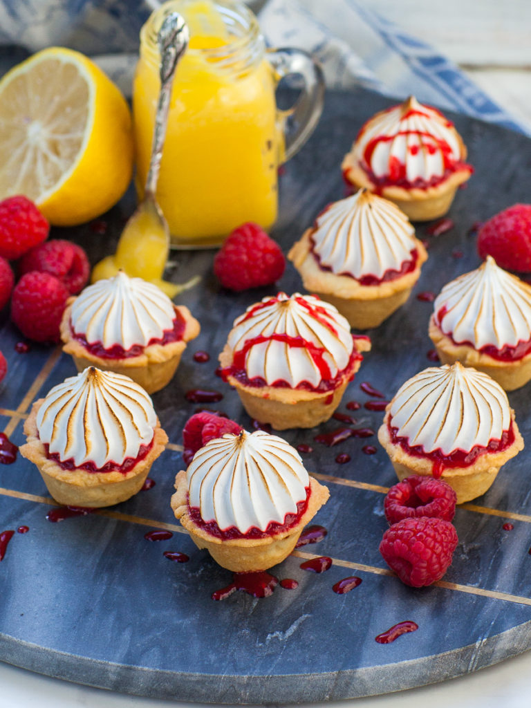 lemon meringue tartlets with raspberry sauce and homemade lemon curd