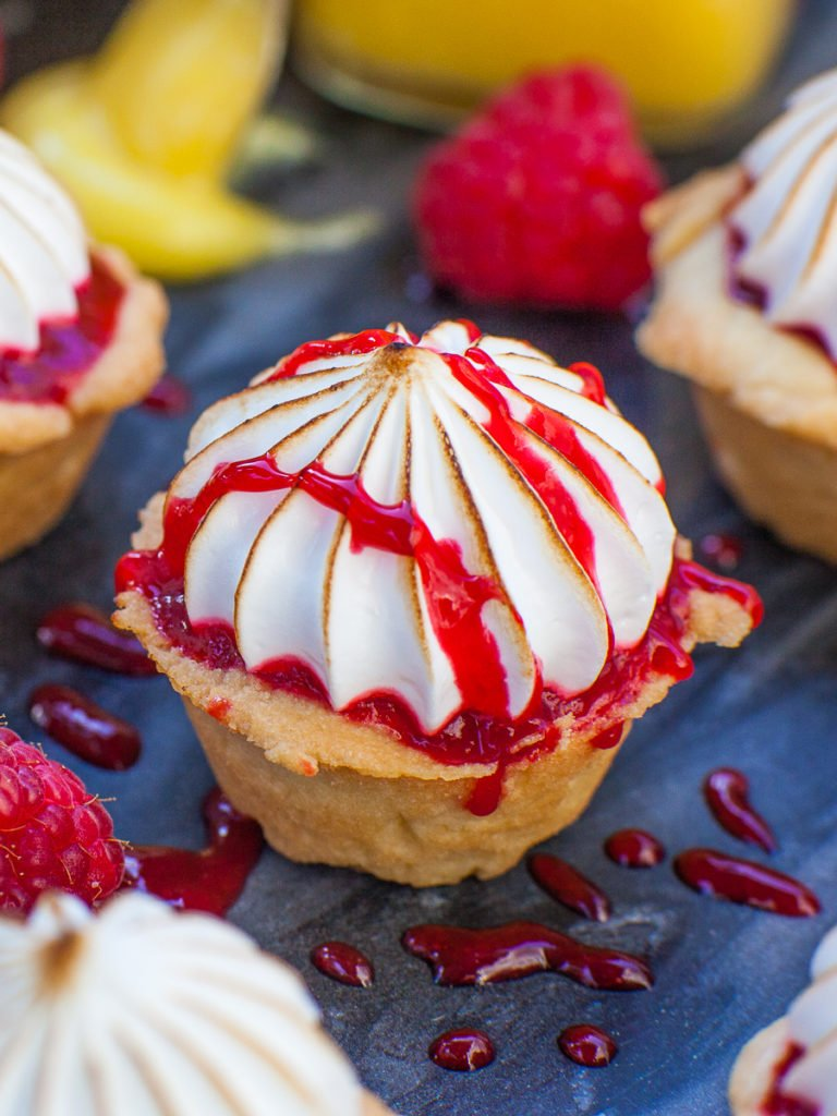 close up of raspberry lemon tartlets with torched meringue topping
