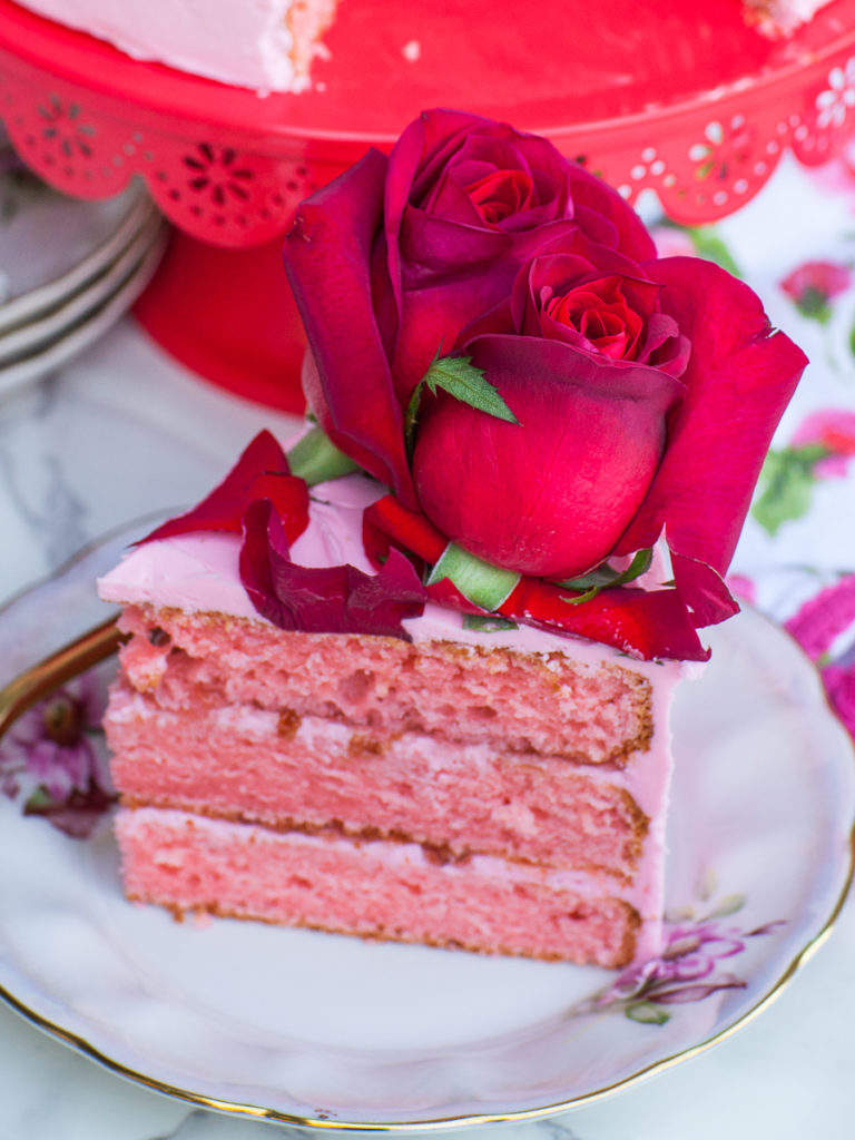 slice of rose cake with red roses on top