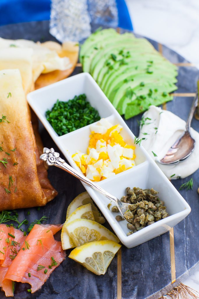 toppings for savory crepes - chopped eggs, capers, chives, salmon, lemon and avocado, sour cream