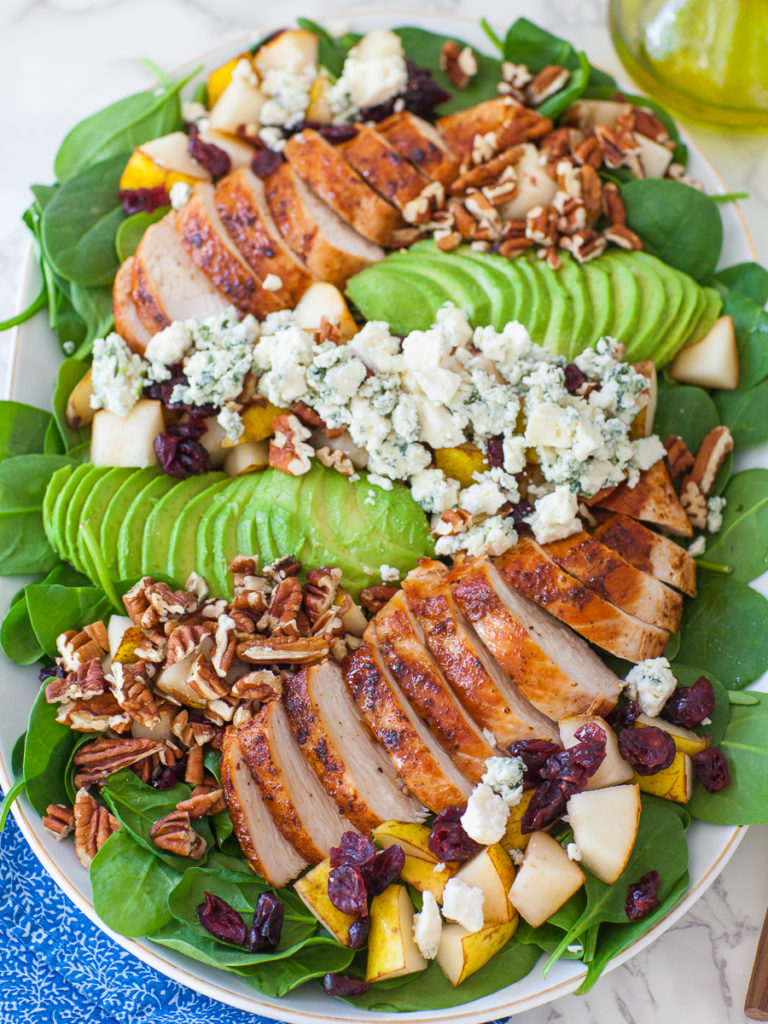 balsamic spinach salad with golden chicken breast, cheese, pears, and balsamic vinaigrette dressing