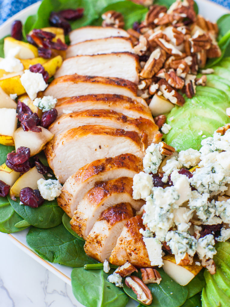 sliced juicy chicken breast over a bed of spinach salad with blue cheese
