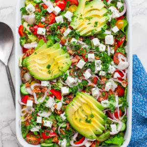 blt salad with avocado and feta cheese in a large casserole tray
