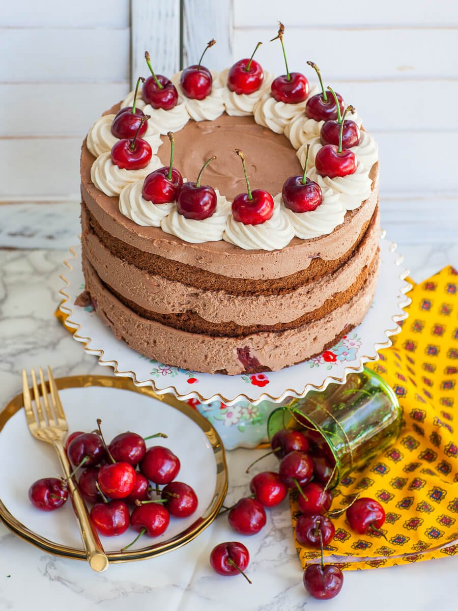 chocolate mousse cake with cherries and whipped cream