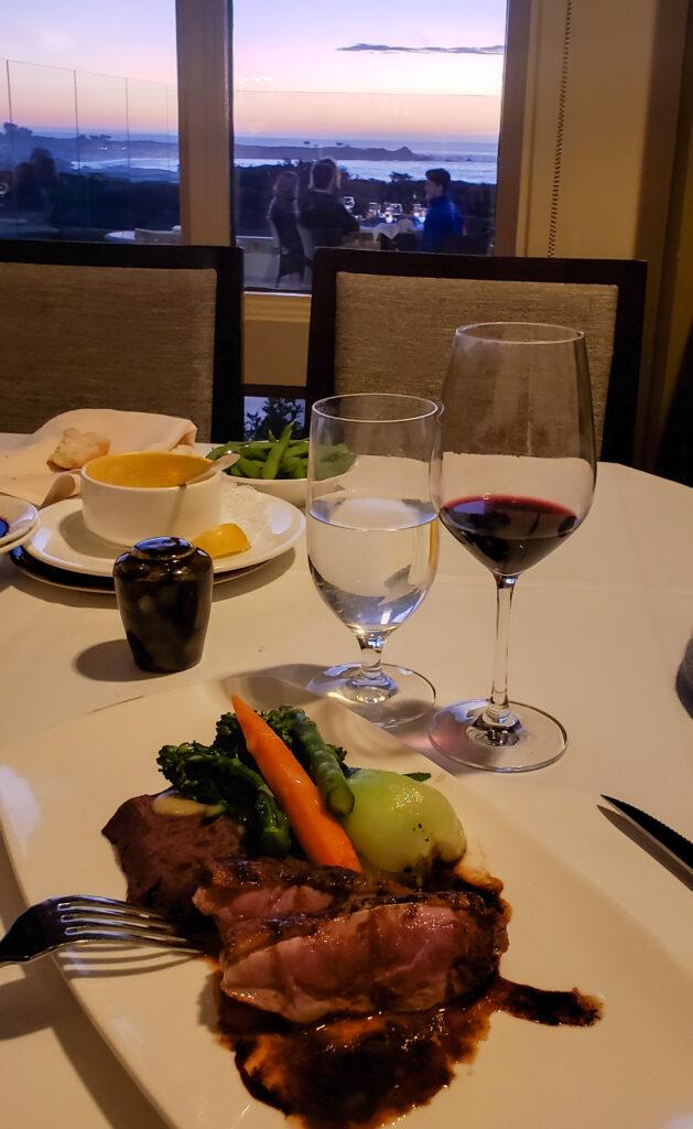 duck breast dinner with red wine overlooking ocean