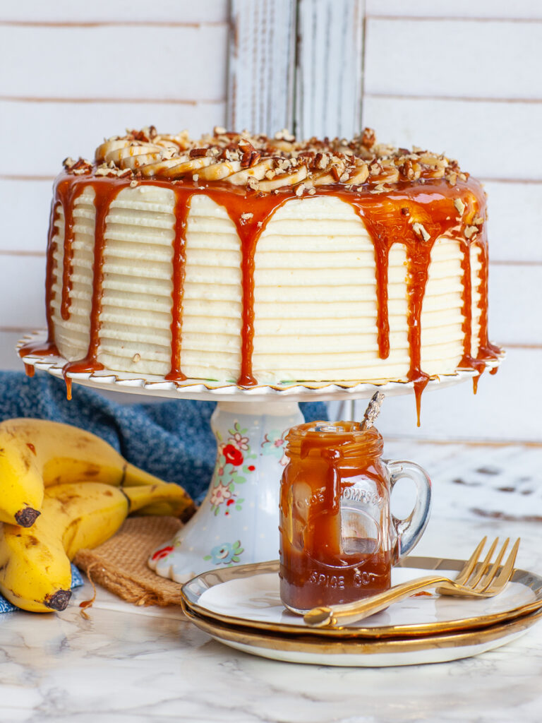 caramel banana cake with cream cheese frosting and caramel drip
