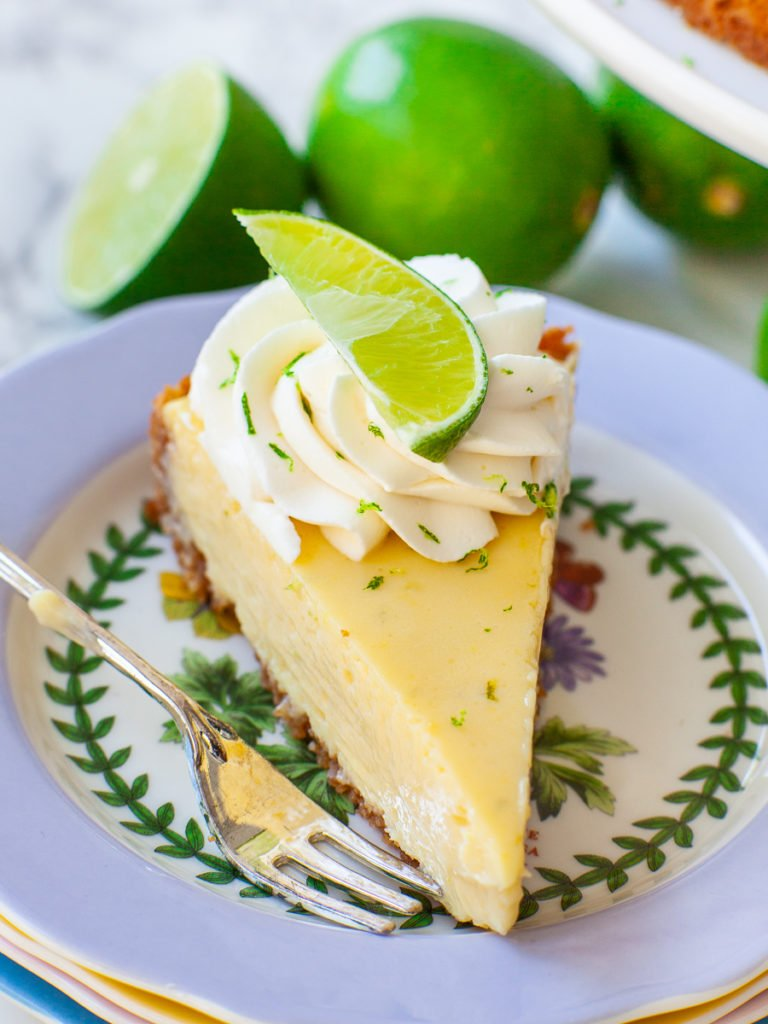 slice of coconut key lime pie with lime wedge, lime zest and whipped cream