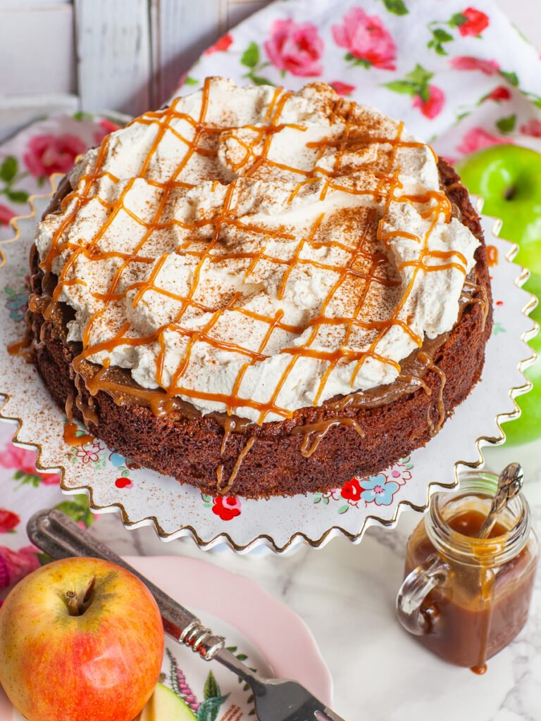 caramel apple cake garnished with whipped cream and caramel drizzle