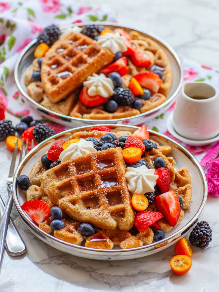cinnamon sugar buttermilk waffles with fruit, whipped cream and maple syrup