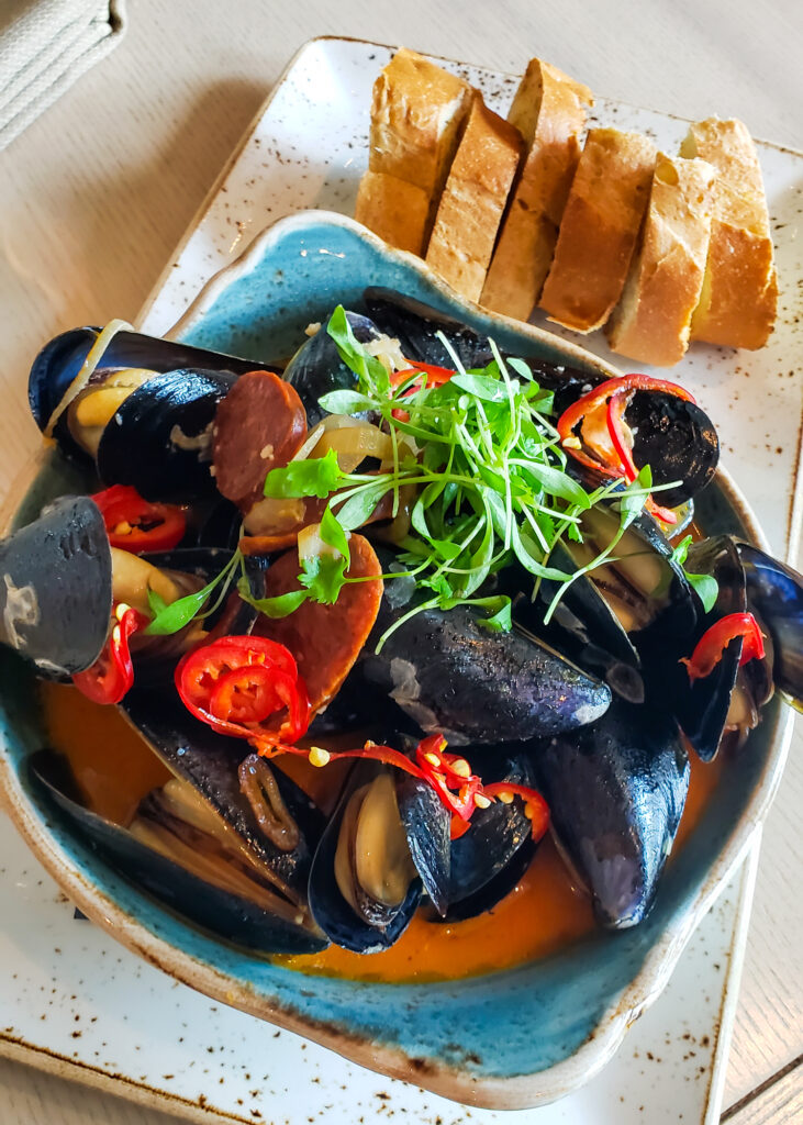 black mussles with sauce, bread and peppers at The Bistro
