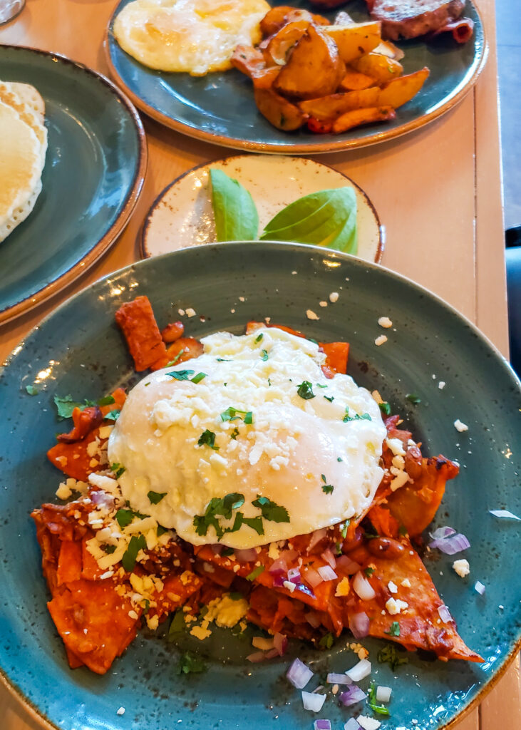 chilaquiles - Mexican breakfast dish with eggs, tortilla chips in tomato sauce