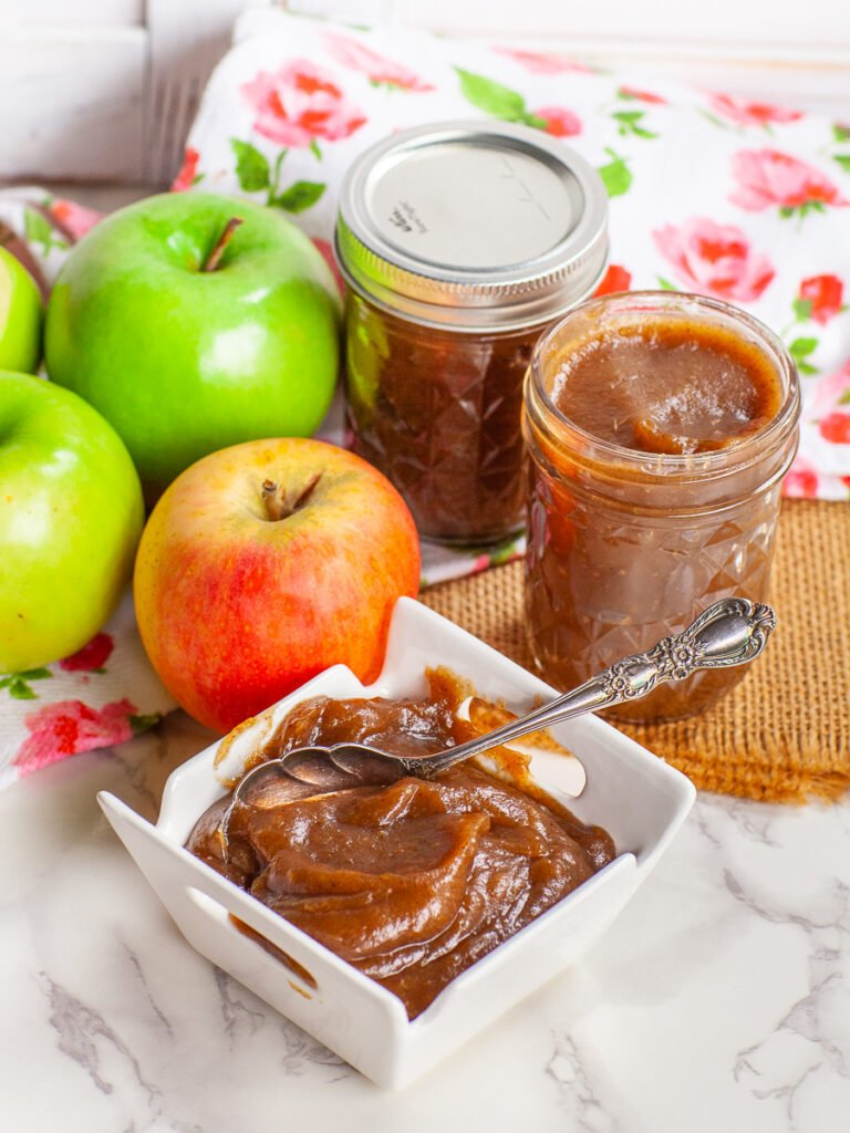 apple butter spread in glass jars and in bowl with green apples