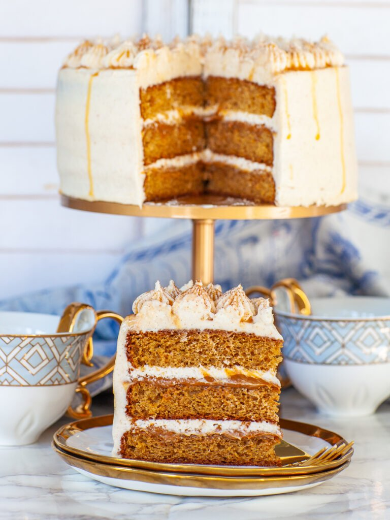 cinnamon roll cake slice with cream cheese frosting and caramel filling