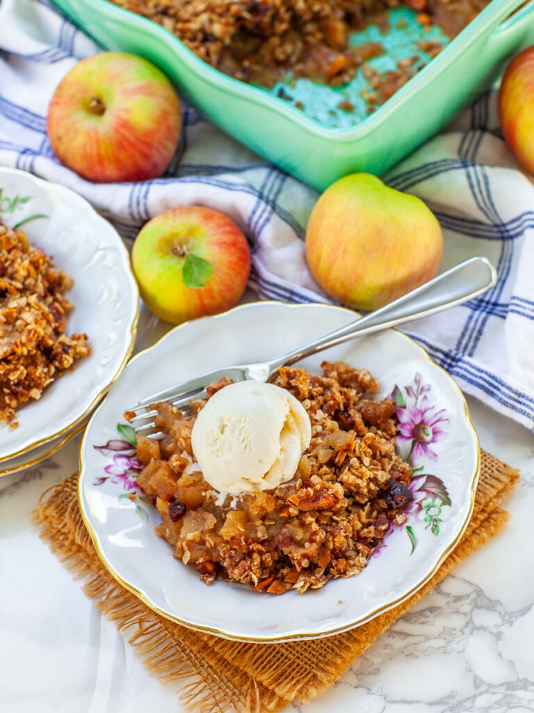 plated apple crisp with almond and cranberry topping, with ice cream