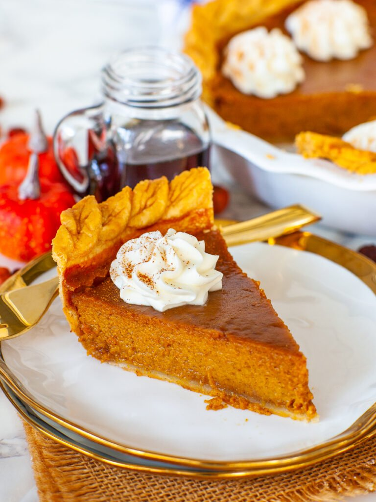 slice of maple pumpkin pie with ground cinnamon and whipped cream