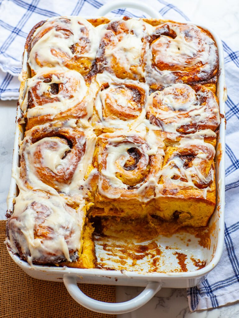 pumpkin cinnamon rolls in casserole pan with cream cheese icing