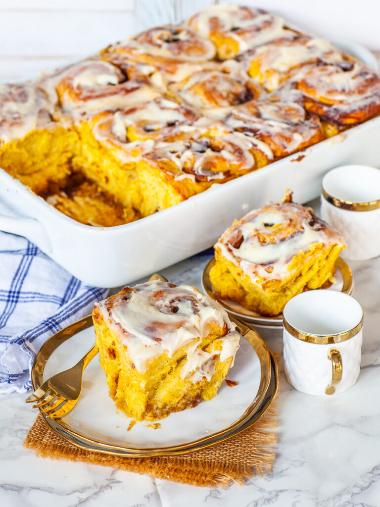 pumpkin cinnamon rolls with cream cheese icing in casserole pan