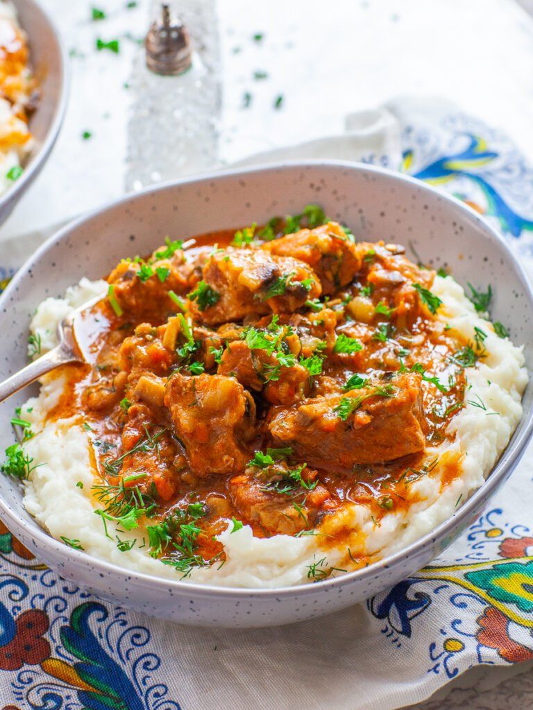 braised pork shoulder with tomato mushroom gravy over mashed potatoes