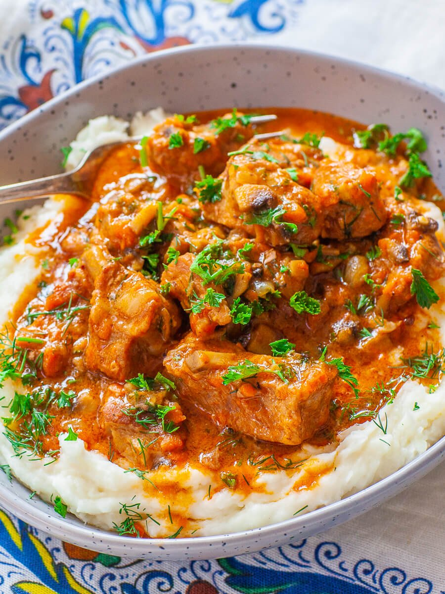 braised pork with tomato mushroom sauce over mashed potatoes with fresh herbs