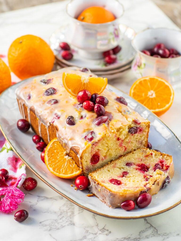 orange cranberry bread recipe with orange glaze on serving platter