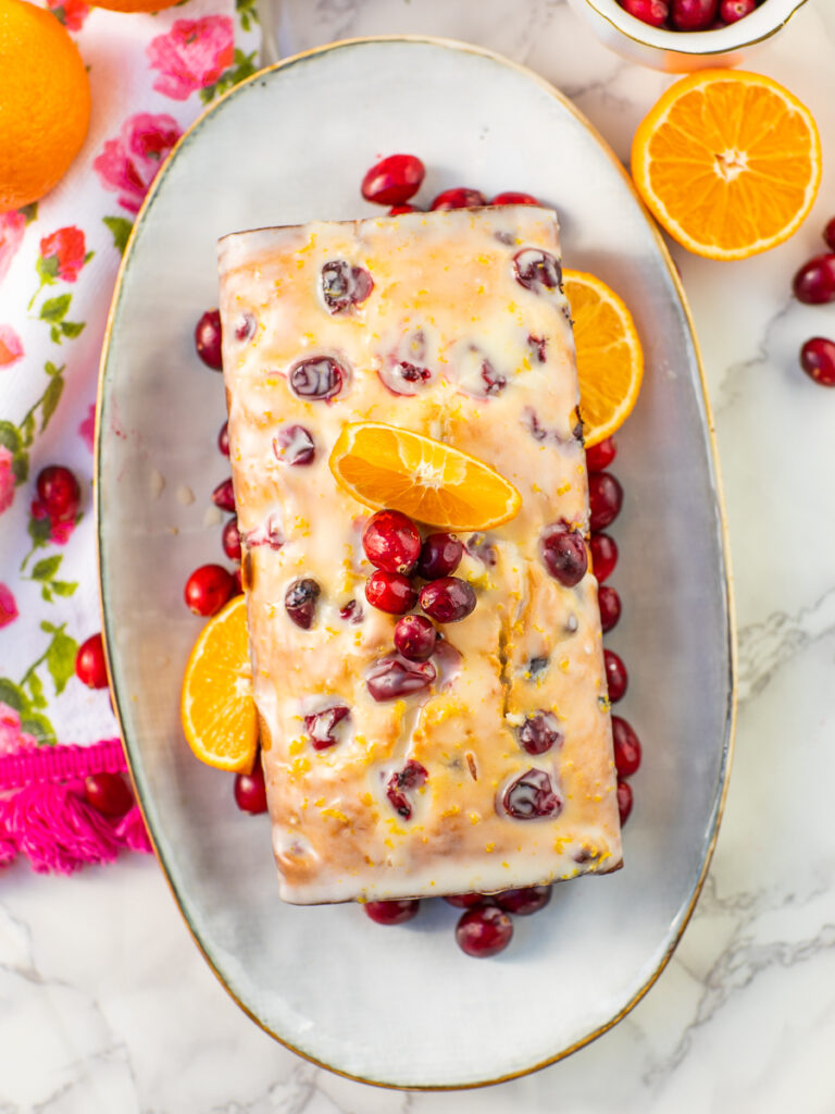 holiday cranberry bread with orange glaze on serving platter with fresh cranberries