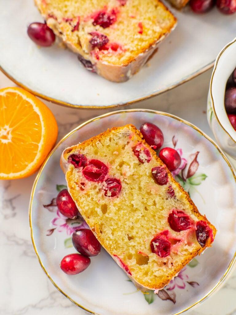 slice of orange cranberry bread with fresh cranberries
